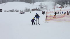 Adorable little kid, learning how to ski with his father Stock Footage