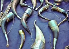original drinking horns antique on blue cloth - stock photo