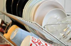 the clean dishes on the rack - stock photo