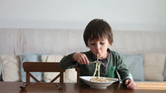 Adorable little boy, eating spaghetti at home, homemade pasta Stock Footage
