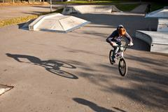 joung red haired boy jumps with his BMX Bike at the skate park - stock photo