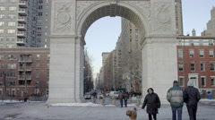 Woman walking dog Washington Square Park arch Empire State Building winter 4K NY Stock Footage