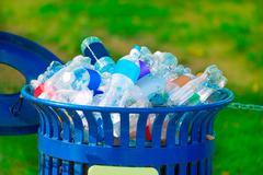 Trash bin full of beverage empty bottles Stock Photos