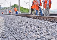 railway embankment, rails and workers in orange vests - stock photo