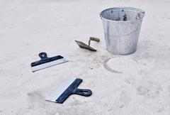 Metal bucket with cement and spatulas Stock Photos