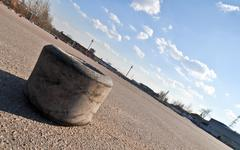 old karting tire on the asphalt of a race track - stock photo