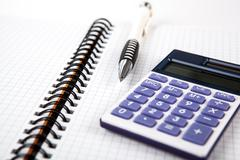 pen on a notebook into a cell and calculator - stock photo