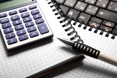Pen with calculator on a notebook and keyboard Stock Photos