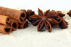 Aromatic close up set of anise and cinnamon on white fibre material like flax Stock Photos
