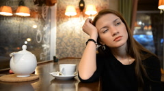Young girl talking with someone in an evening bar, restaurant, cafe Stock Footage