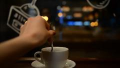 Young girl drinking tea in a cafe in the evening Stock Footage