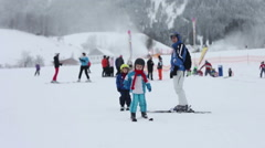 Adorable little kid, learning how to ski with his father - stock footage