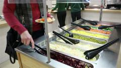 A woman taking vegetables in the salad bar. Lunch in the canteen. Stock Footage