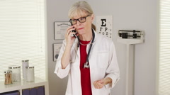 Mature woman doctor smartphone talking Stock Footage