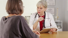 Senior woman doctor talking patient at desk Stock Footage