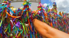 Guy making a wish with the colorful religious brazilian ribbons Fita do Bonfim Stock Footage