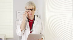 Senior woman doctor using smartphone tablet Stock Footage