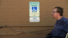Caucasian Man in wheelchair passes handicap parking sign in lot Stock Footage