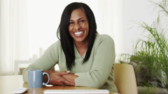 Happy laughing senior black woman sitting at desk Stock Footage