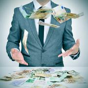 Man trying to catch money falling from the sky Stock Photos