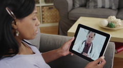 Senior african patient listening to doctor talk on tablet Stock Footage