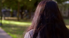 Teen Girl Walking Through City Park, She Looks Around, Daydreaming Stock Footage