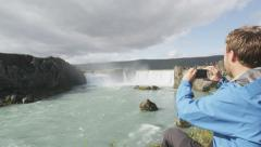 Tourist taking photo of waterfall Godafoss Iceland - Man taking phone picture Stock Footage
