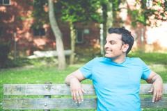 Man in blue shirt chilling on bench - stock photo