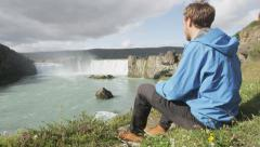 Hiker relaxing hiking - waterfall Godafoss Iceland Stock Footage