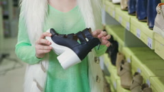 Happy young woman shopping for sports shoes Stock Footage