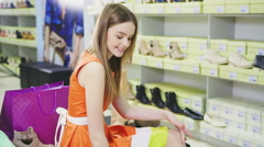 Video of lady trying on several pairs of new shoes in the mall Stock Footage
