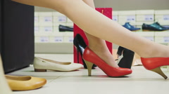 Young woman trying on shoes in shop - stock footage
