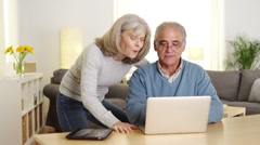 Senior adults using laptop computer at desk - stock footage