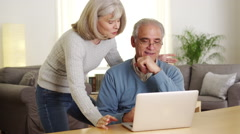 Senior couple using laptop computer together Stock Footage