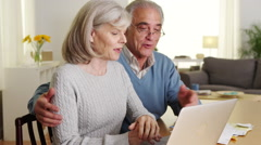 Happy senior couple using laptop computer to pay bills - stock footage