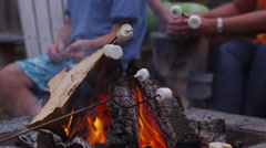 Closeup, roasting marshmallows by outdoor fire. Shot on RED EPIC for high Stock Footage