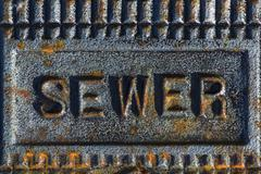 Sewer access cover with rusty iron - stock photo