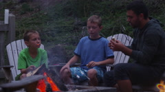 Family roasting marshmallows by outdoor fire. Shot on RED EPIC for high quality - stock footage