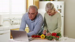 Stock Video Footage of Senior couple using laptop recipes cutting vegetables in kitchen