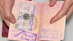 Man's hands turning the pages of the passports with visas and stamps Stock Footage