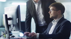 Two Businessmen Have Discussion on Workplace next to Computer Stock Footage