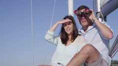 Young couple on sailboat together looking through binoculars. Shot on RED EPIC Stock Footage