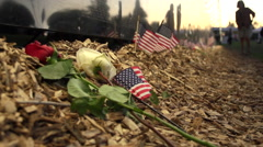 Close up of flowers and flags next to Vietnam Wall That Heals. Stock Footage
