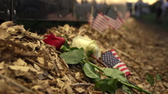 Rac focus close up of flowers and flags next to Vietnam Wall That Heals. Stock Footage