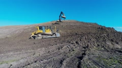 Yellow  excavator and a bulldozer moving earth on a hill Stock Footage