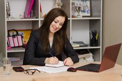 Female office worker grinning writing in a notebook for your desktop Stock Photos