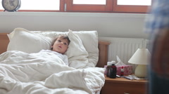 Sick boy, lying in bed, mother checking his temperature and giving him medicine Stock Footage