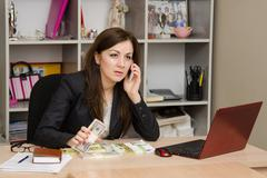 Amazed girl holding a wad of money and talking on phone in office Stock Photos