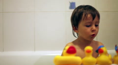 Adorable little boy, playing in the bathtub with rubber ducks Stock Footage
