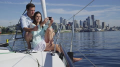 Young couple on sailboat together using cell phone. Shot on RED EPIC for high Stock Footage
